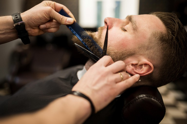Profile portrait of young man having beard trimmed at barber salon