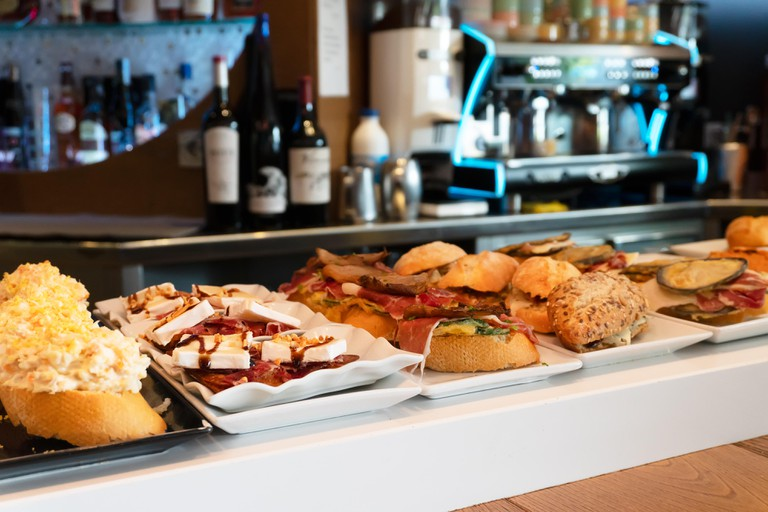 Spanish tapas or pintxos on display on the counter of a bar