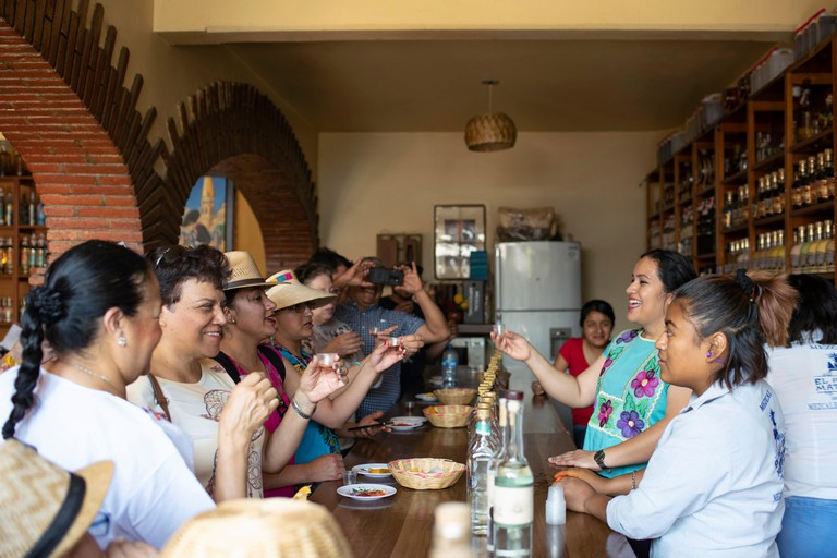 Tourists enjoying Mezcal tasting at 'El Rey de Matatlan' distillery and shop. Teotitlan del Valle, Oaxaca State, Mexico. Apr 2019
