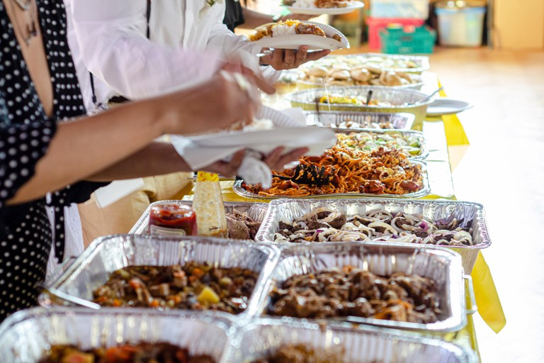 A self service buffet of Filipino dishes at a party.