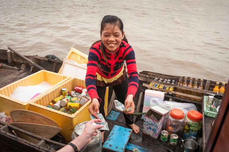 Young girl selling drinks from a boat in the floating market, Cai Rang near Can Tho, Mekong River Delta, Vietnam