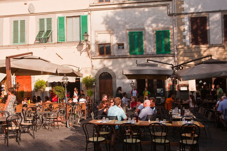 People eating at a restaurant in Piazza santo Sprito in Florence, Italy.
