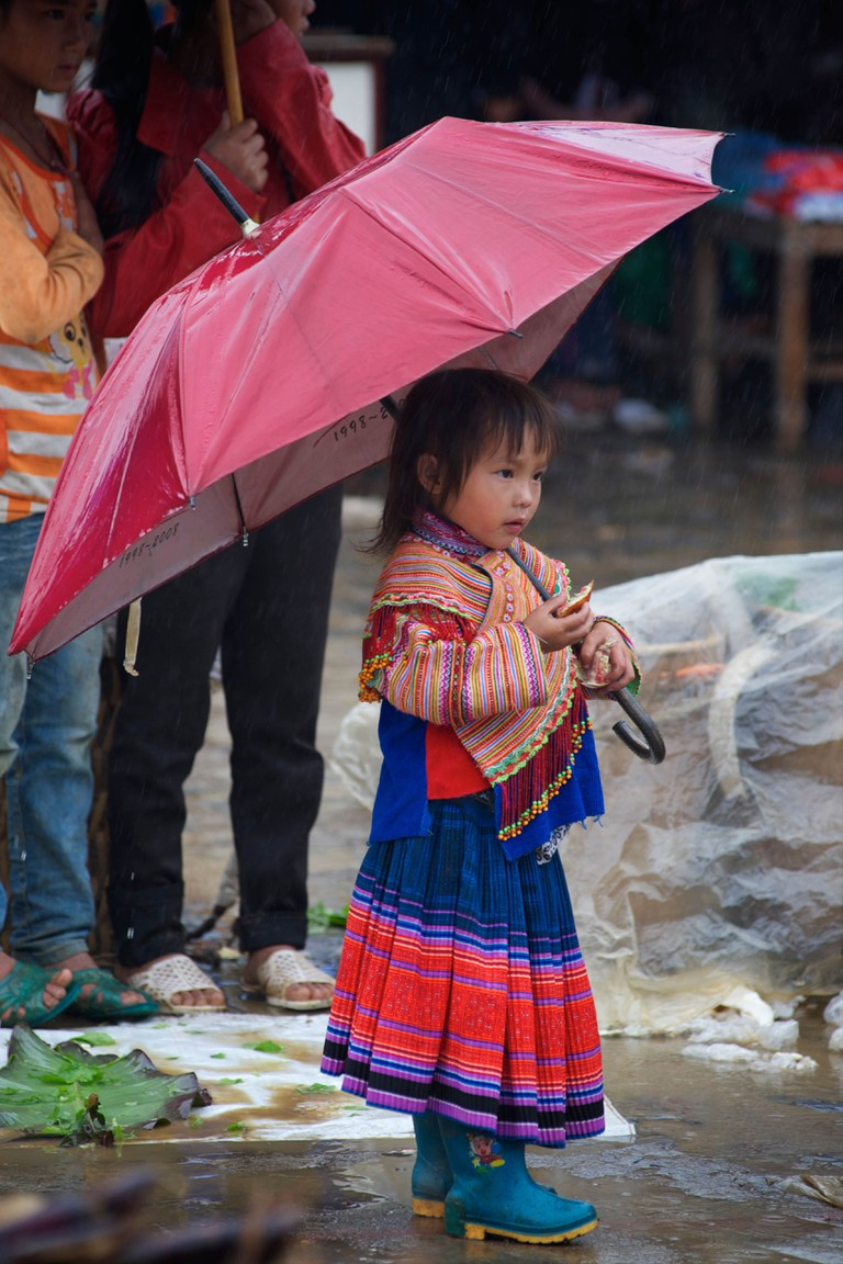Flower Hmong child holding an umbrella to shield her grandmother from the rain, Bac Ha, Lao Cai province, Vietnam