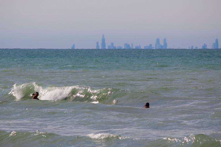 Bathers wade in the surf at Indiana Dunes State Park with downtown Chicago on the distant horizon, the earth's curvature obscuring lower buildings.