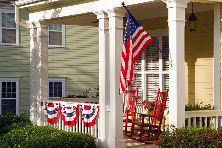 An American Flag and buntings hang from a front porch of an upscale, Victorian home in celebration of the upcoming holiday