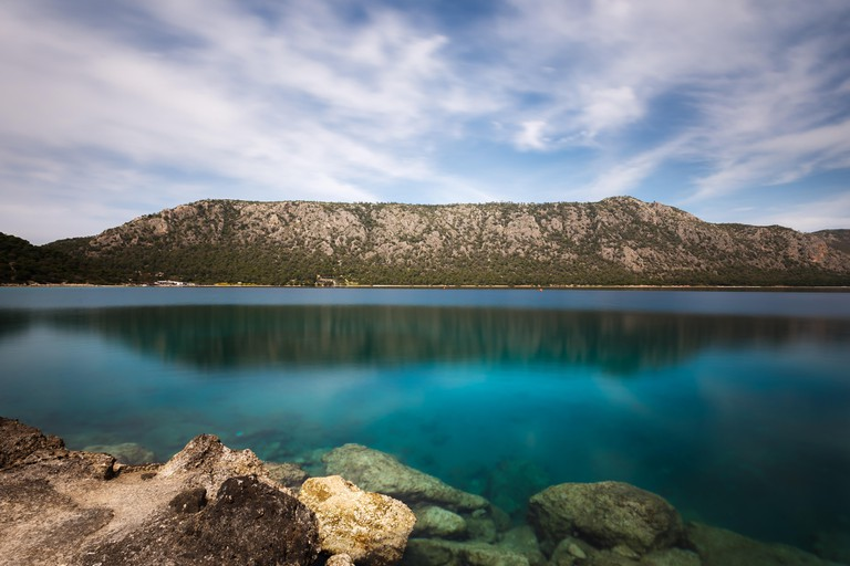 Beautiful crystal clear waters of Vouliagmeni Lake near Loutraki, Greece against a cloudy sky