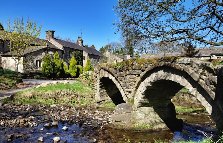 Thirteenth century packhorse bridge and the village of Wycoller.