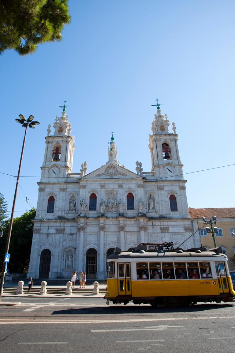 A Tram 28 passing in front of Basilica da Estrela, Lisbon, Portugal.