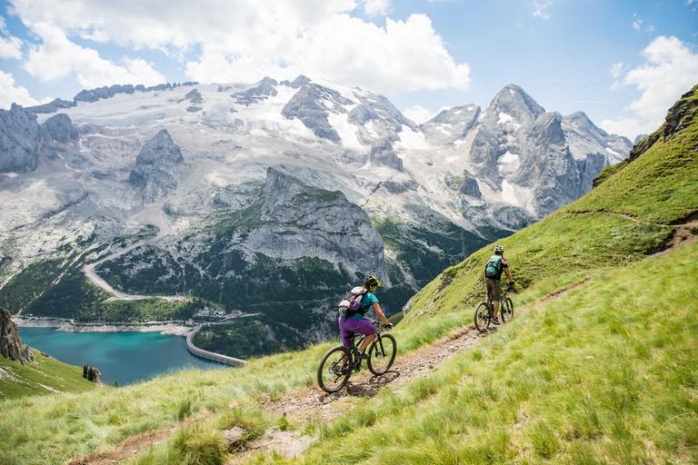 Man and woman mountain biking near Marmolada Glacier, Dolomite mountains, Italy
