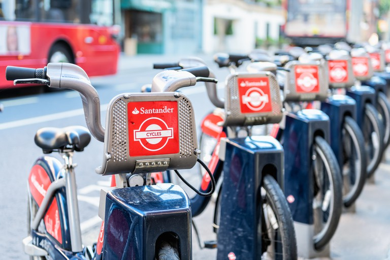 Many Santander Cycles red bikes for hire, rent, rental standing, parked at docking station in downtown in row by street, road, sidewalk