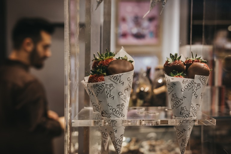 Chocolate covered strawberries on retail window display of Godiva shop