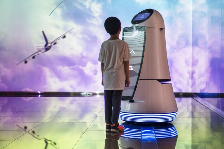 A young boy communicating with a robot that is on display at
