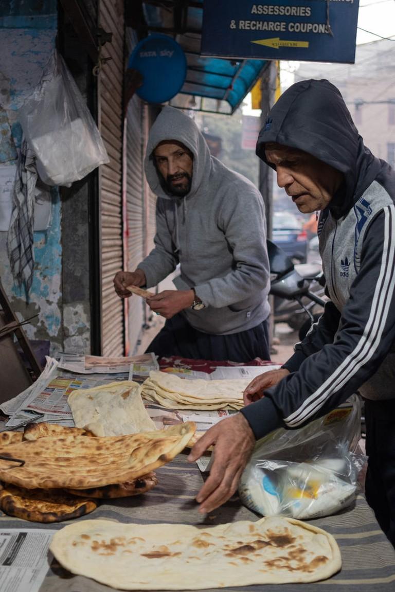 Customers buy freshly baked bread at an Afghan bakery at Bhogal market in Delhi