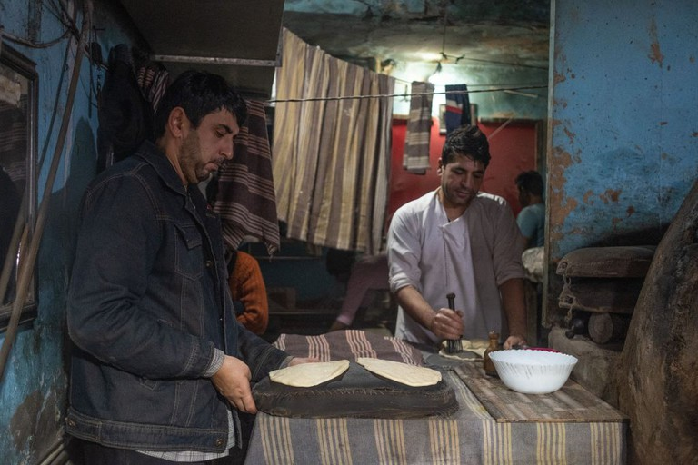 Afghan bakers prepare bread dough before baking it in a clay oven at a market in Delhi.