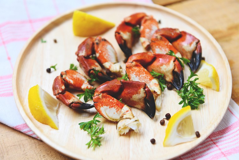 Red stone crab claw - Cooked crabs boiled on wooden plate with lemon on plate served seafood
