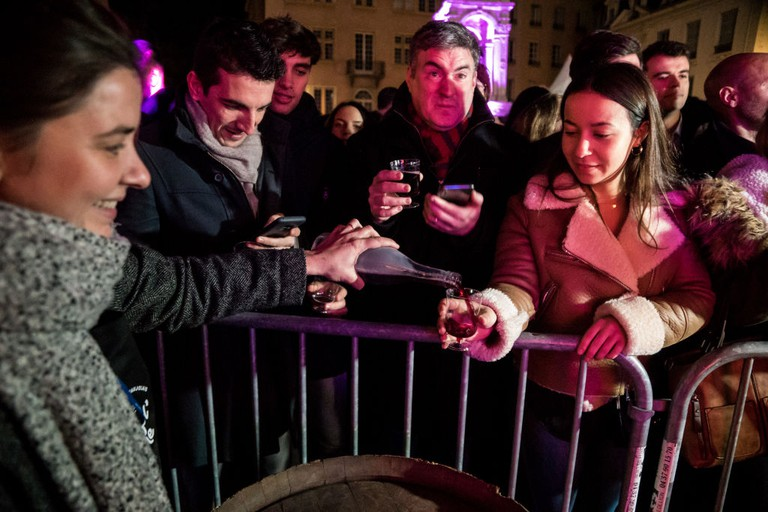 People celebrate the first barrel of Beaujolais Nouveau in Lyon
