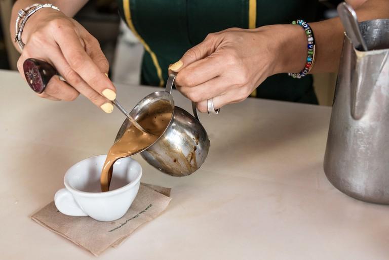 Woman serving a cuban coffee
