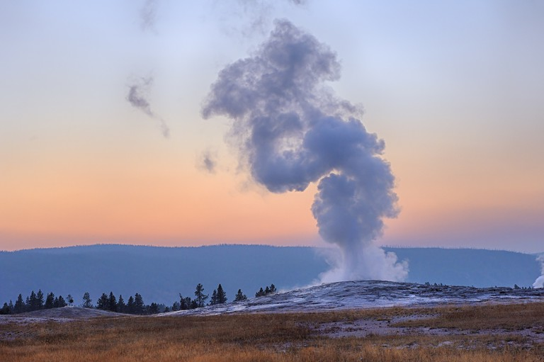 USA, Wyoming, Yellowstone National Park, Old Faithful Geyser erupting at sunset