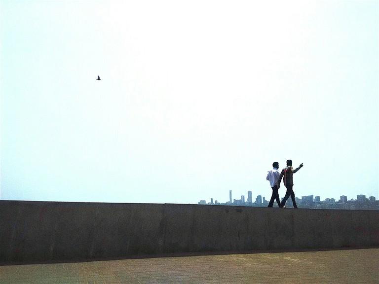 Two Men Walking At Edge Of Wall On City Pavement, Mumbai