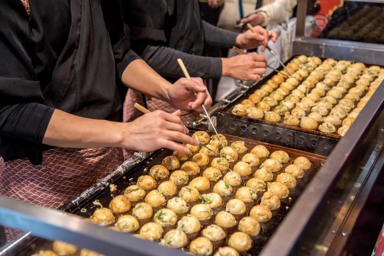 Cooking Takoyaki on hot pan in Osaka Japan