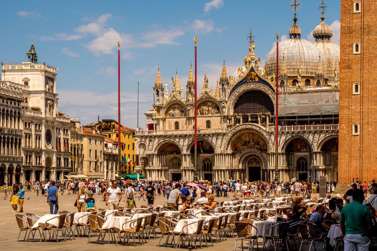 St Mark.s basilica with tables and chairs from Cafe Florian in the foreground. Venice, Italy.