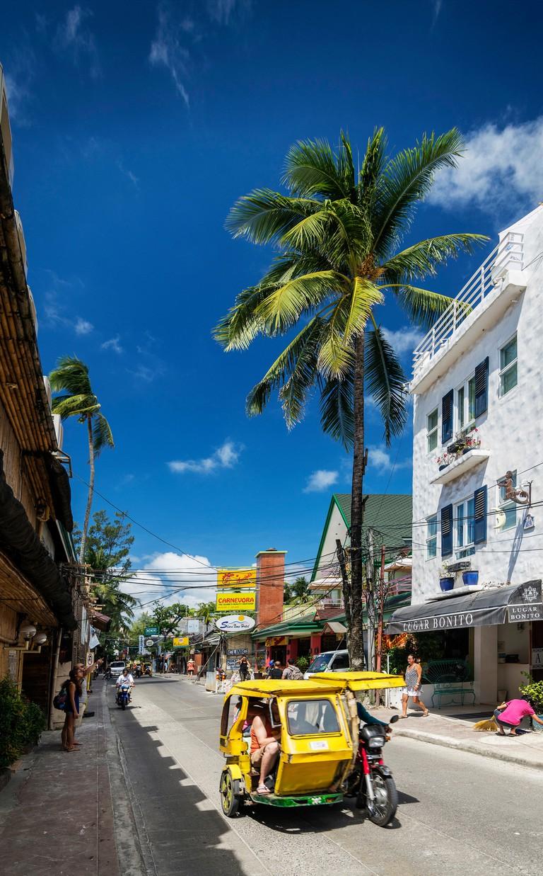 road and colourful local tuk tuk moto taxi on exotic tropical boracay island philippines