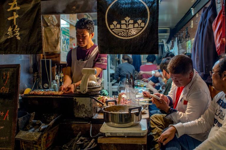 Restaurant in Shonben Yokocho with man cooking and customers. Tokyo streets at night. Shinjuku, Tokyo, Japan