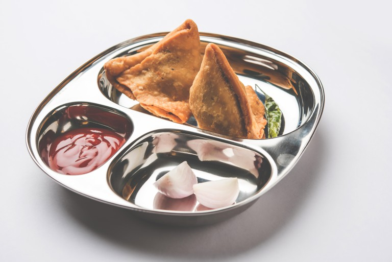 Samosa - Indian deep fried junk but tasty food or snacks served in stainless steel plate over white background with tomato ketchup and green fried chi
