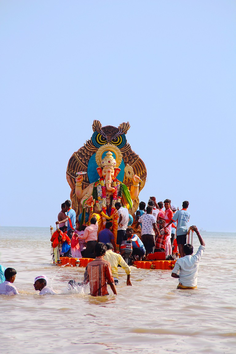 Huge Ganapati idol taken for immersion to the sea in wooden boats, Chowpatty, Mumbai