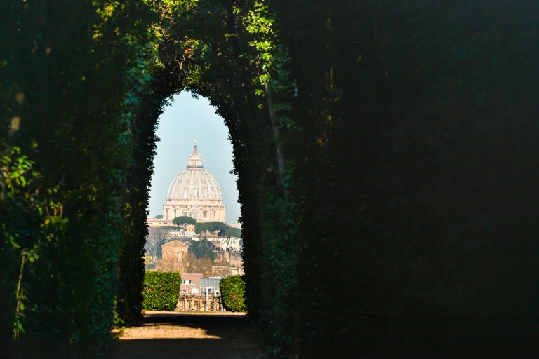 The Aventine Keyhole. Views of St Peter's Cathedral seen through peephole of door of the Priory of the Knights of Malta, Aventine Hill, Rome, Italy.