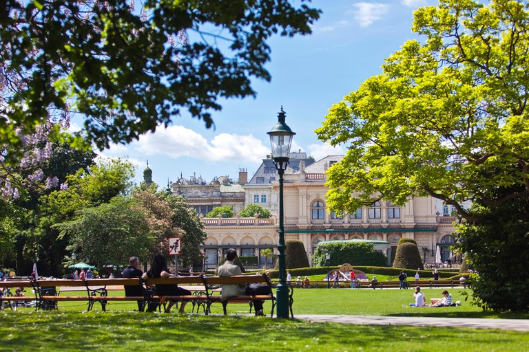 VIENNA, AUSTRIA - MAY 6, 2012: Some people enjoy a sunny recreational day at the Stadtpark Vienna with the Kursalon
