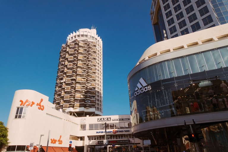The distinct white and brown cylindrical tower of Dizengoff Center