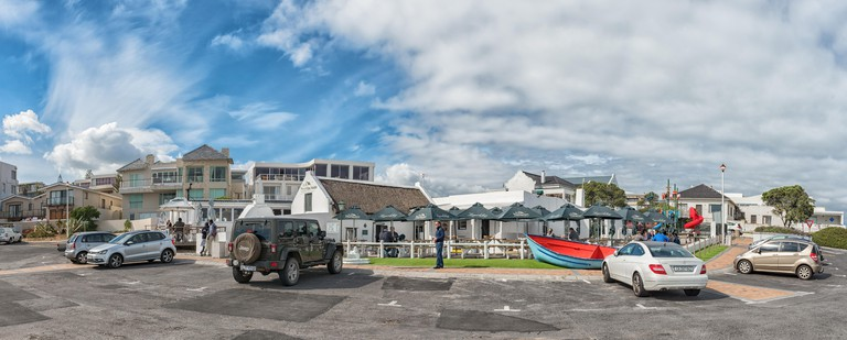 CAPE TOWN, SOUTH AFRICA, AUGUST 14, 2018: Ons Huisie, a beachfront restaurant in Bloubergstrand. Vehicles and people are visible