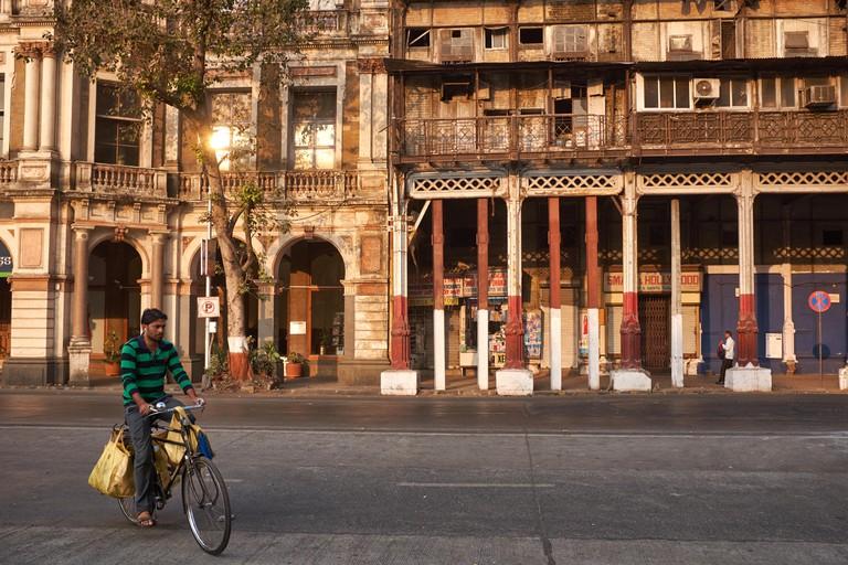 A cyclist passes 19th century Esplanade Mansion, Mumbai, originally Watson's Hotel, the first luxury hotel in Kala Ghoda, Fort, Mumbai / Bombay, India