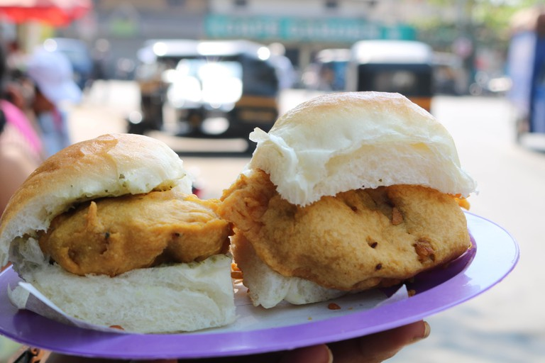 The Street Food That Defines Mumbai. ... A pillowy pav, stuffed with a golden-fried spiced batata (potato) vada, covered with a lick of tamarind and coriander chutneys