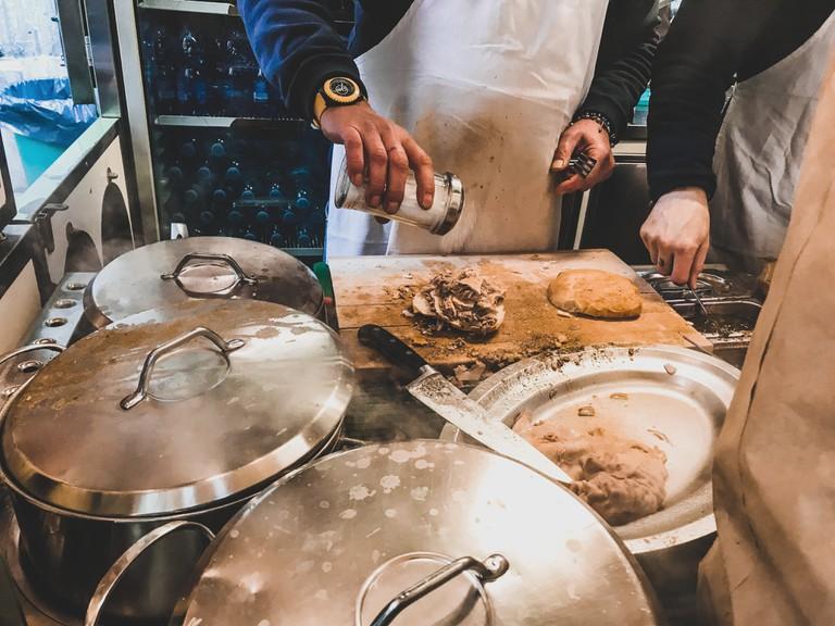 An Italian chef prepares lampredotto sandwich of Florence
