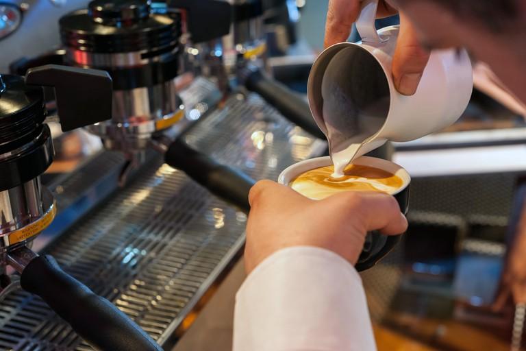Puoring milk in a coffee cup, preparing italian cappuccino, with professional espresso machine