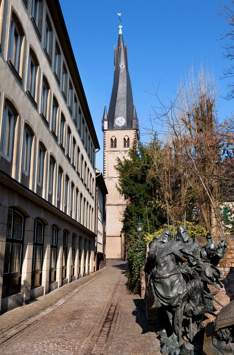 View of the city street, St. Lambertus Basilica and part of the The Stadterhebungsmonument monument in Dusseldorf city, Germany