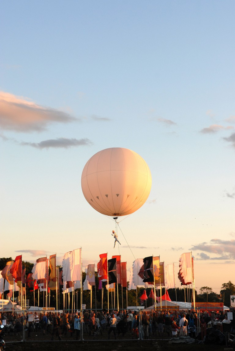 Heliosphere balloon and dancer performing in the air above WOMAD Festival