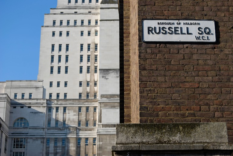 street name sign for russell square with senate house, part of the university of london, in background to left