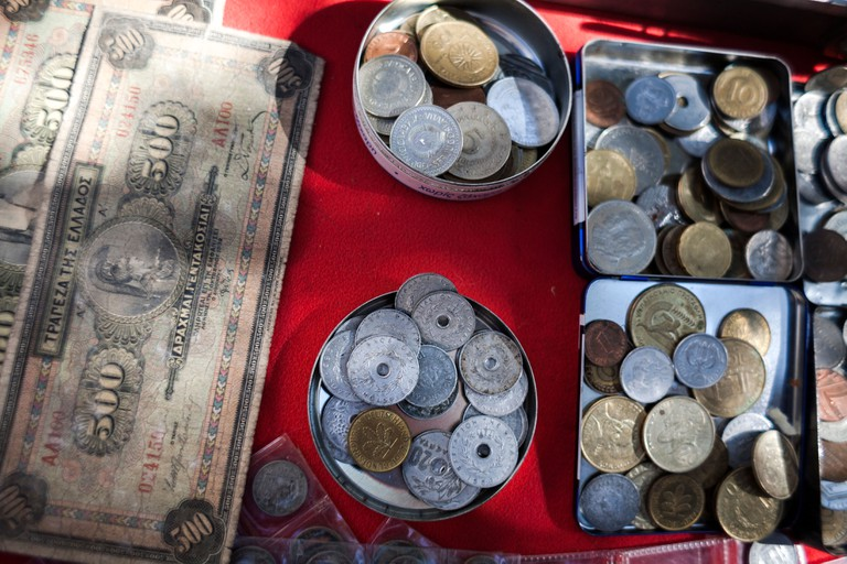 Old Greek drachma coins and bank notes for sale during Saturday antique bazaar in Bit Bazaar antiques street market in Salonika
