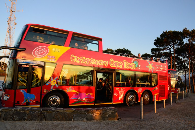 Topless red bus with tourists viewing sunset over Atlantic Ocean at Signal Hill, Cape Town, South Africa