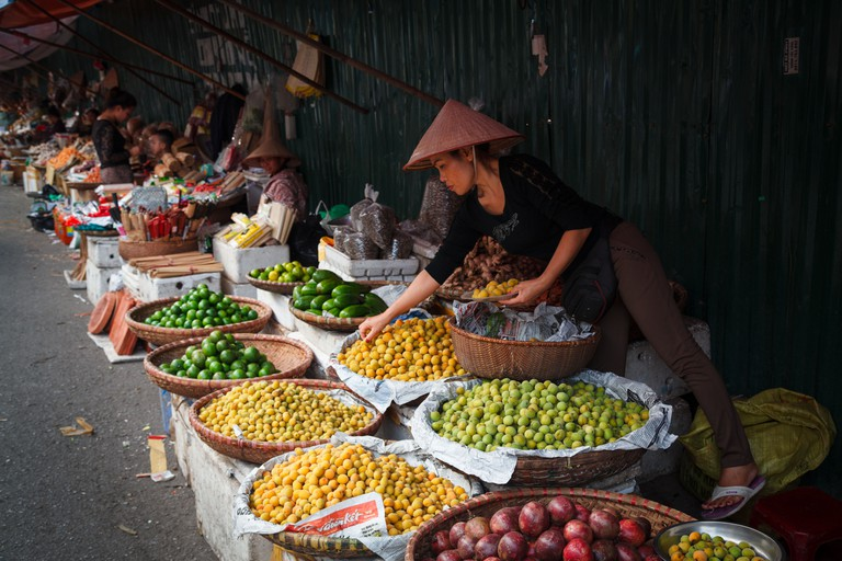 A market vendor selling fruit outside the Dong Xuan Market in the Old Quarter, Hanoi