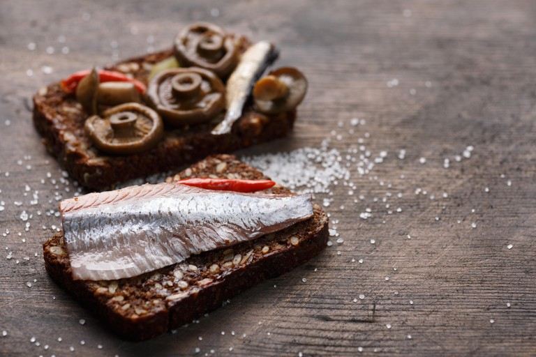 Two different open sandwiches from dense wholegrain rye bread (rugbrod) with wild pickled mushrooms, sprats and herrring on aged