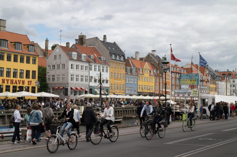 Cyclists passing the colourful houses containing bars and restaurants at the canal at Nyhavn New Harbour Copenhagen Denmark