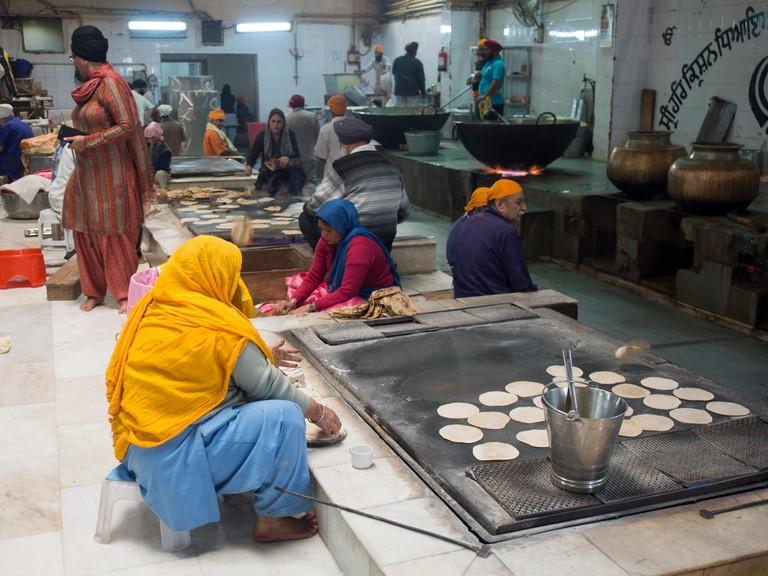Women baking bread at Gurudwara Bangla Sahib shrine