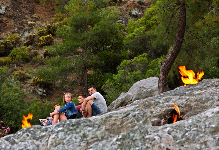 Tourists rest by the flames of the Chimaera