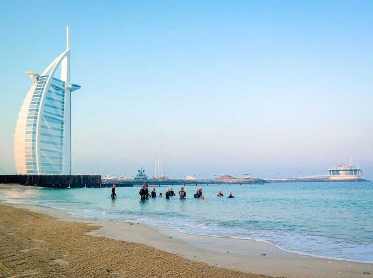 Scuba divers diving under water next to Burj Al Arab on an early morning day in Dubai