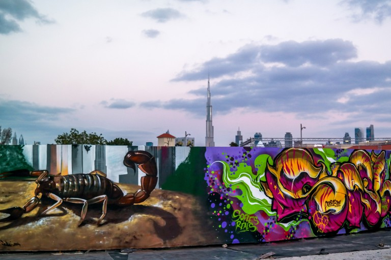 Graffiti art displayed on walls in Dubai with Burj Khalifa and the Dubai skyline in the Background on a cloudy day.