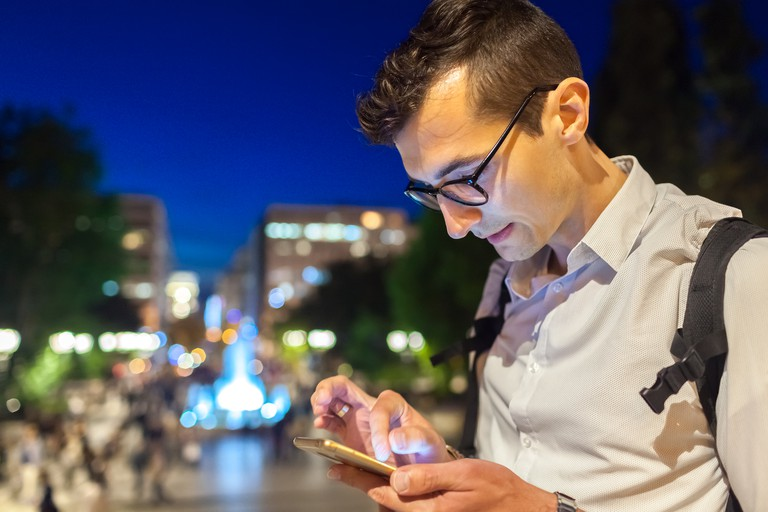 Man using smartphone on city street in Athens, Greece at night. Guy writing message in park